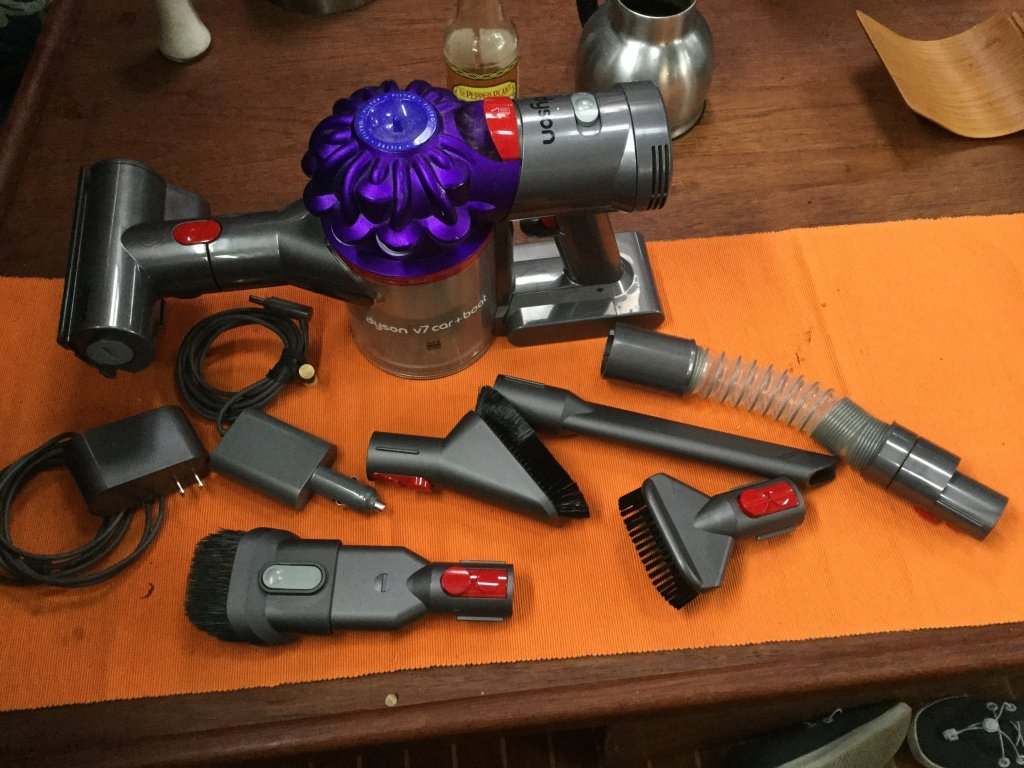 The Dyson V7 Car + Boat Vacuum with six different cleaning heads and a 12 volt car charger and a 110 charge cord.