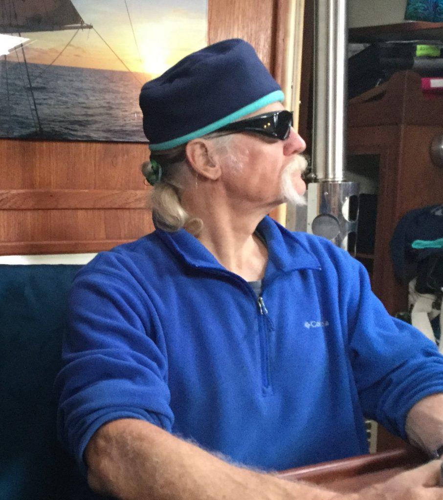 Jon wears a kepi-style cap in dark blue with sea-green trim along the brow
