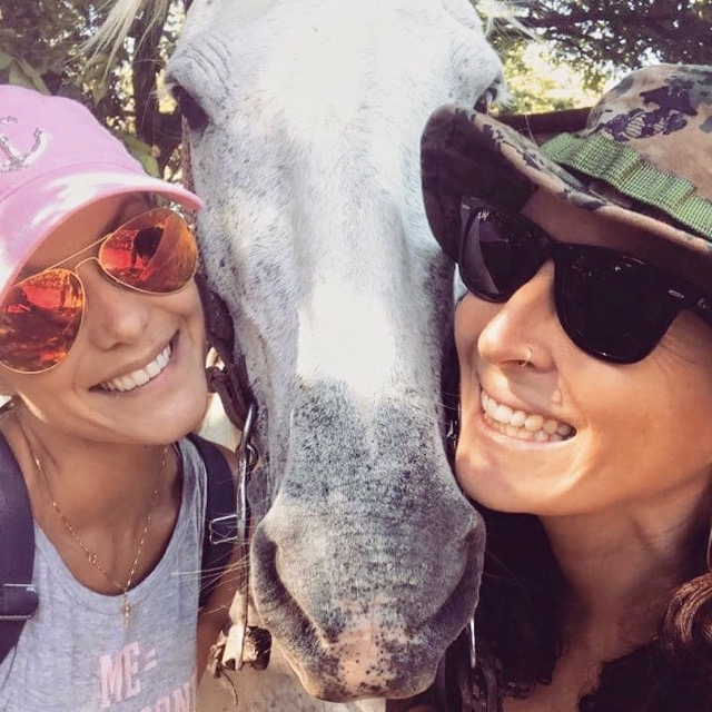 Photo of 2 girls posing for a picture with a horse.