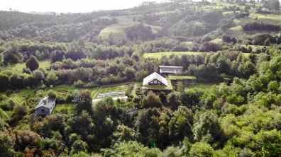The family farmhouse is surrounded by vegetable gardens and forest
