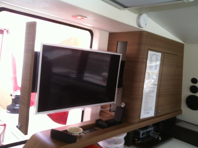 The TV sill slide out from behind the cupboards. The panel attached to the left side of the TV in this picture will be a door that hinges open on Wildling