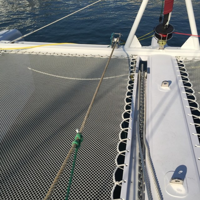 Attach a pulling line to the mooring line using a rolling hitch so you can use the anchor windlass capstan to tension the mooring line