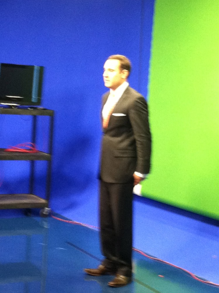 Zach Daniel getting ready for a segment in front of the green screen.