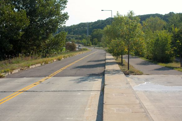 Now an eastern extension of Randolph Avenue, this was Shepard Road prior to the mid-1990s realignment. On the left, two-way traffic now flows on the old Shepard's westbound lanes. What were the eastbound lanes are now a walking/biking lane to the right of the cement island.