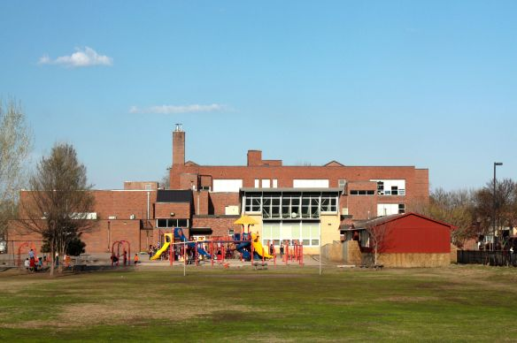 This picture was taken looking east from Pleasant Avenue. A closer examination of the building allows you to see the jumble of additions. On the left, a 1974 appendage; the three story structure in the center is the original 1924 building; in front of that, with the metal grid work is a more recent wing; and on the right is a 1960 or '70s era portable classroom.