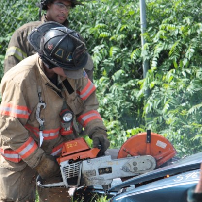A firefighter practices cutting the hood of a car with the Excel or circular saw.