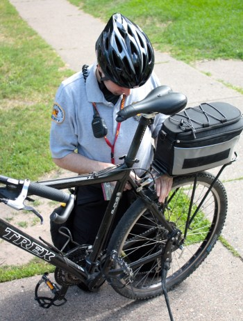 A U of M security officer makes a repair to his bike before heading back to the Minneapolis campus.