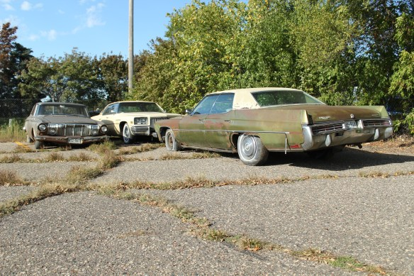 Three old cars sit in a corner of the parking lot bordered by Stewart Avenue, Davern and Shepard Road.