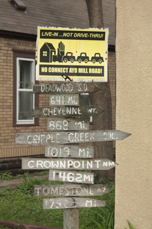 "The yellow and black sign is in protest of a proposal to directly connect the nearby Ayd Mill Road to I-94. The distance markers below it point toward various cities and towns to the west. Cripple Creek is a small Colorado town near the base of Pike's Peak made famous in a 1969 song by the band ""The Band"".)"