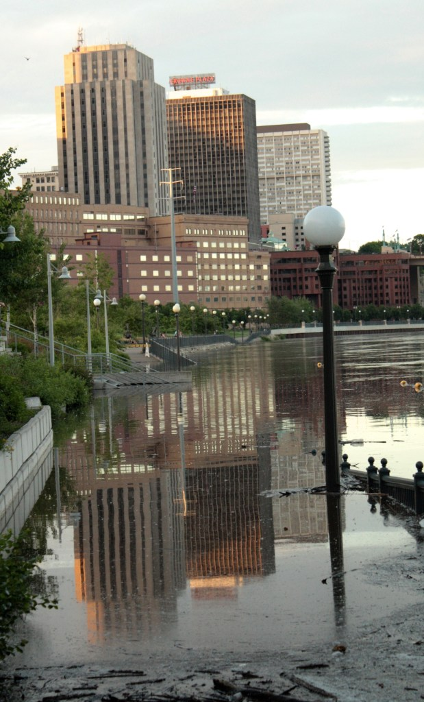 Downtown buildings are reflected in water that crept up a riverfront walking path. Notice the railing on the right gradually descends into the water.