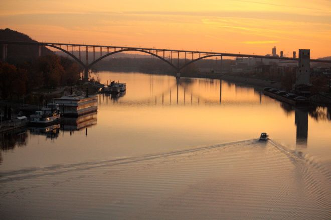 The fading sunlight lends an orange tint to the Mississippi River and the Minnesota Centennial Showboat, left. The Smith Avenue High Bridge is in the middle of the picture.