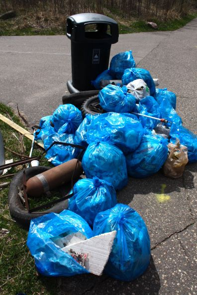 A used spare tire, a rusting fire extinguisher and bags full of discarded paper, plastic, glass and cans collected from the Hollow await disposal.