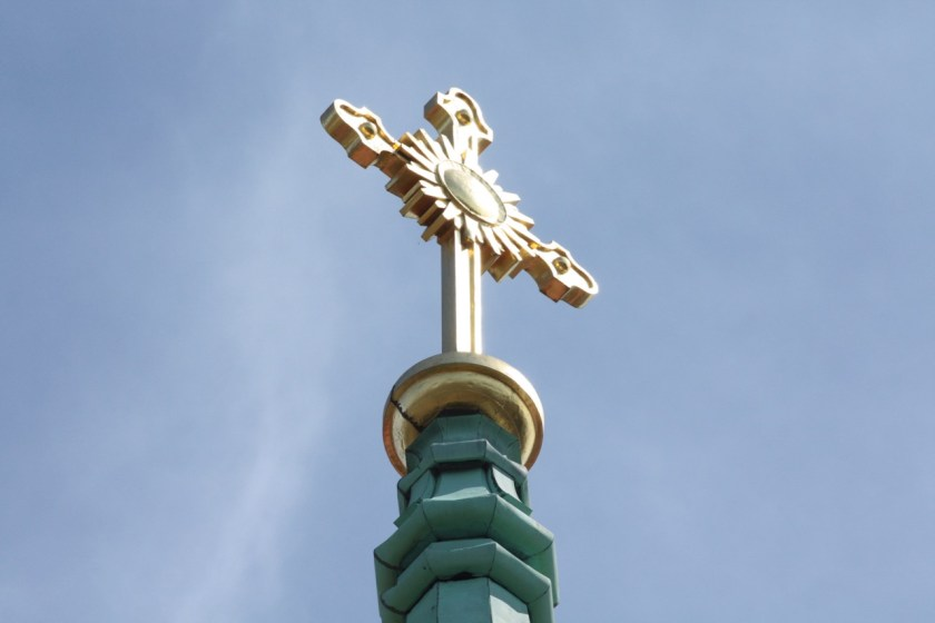 The gold cross at the top of the bell tower shimmered in the midday sun.