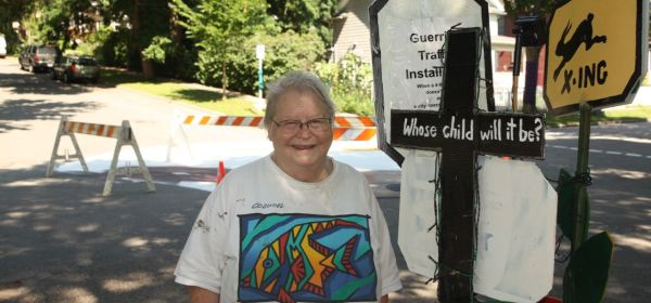 "Sage Holban stands next to the ""guerilla traffic"" stop. Behind her is the unfinished pavement painting."