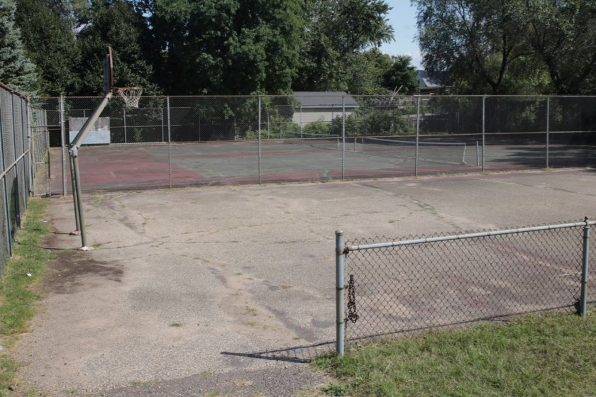 The worn basketball court, foreground, and the two tennis courts, background, at Mounds Park.