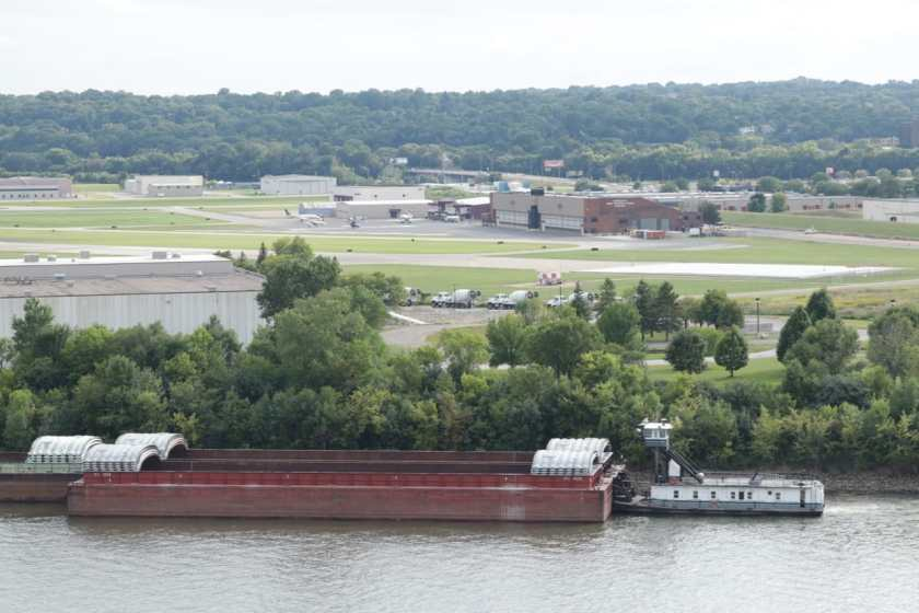 A tug and empty barges head downstream on the Mississippi. In the background is St. Paul Downtown Airport (Holman Field) runways and Minnesota National Guard hangars.