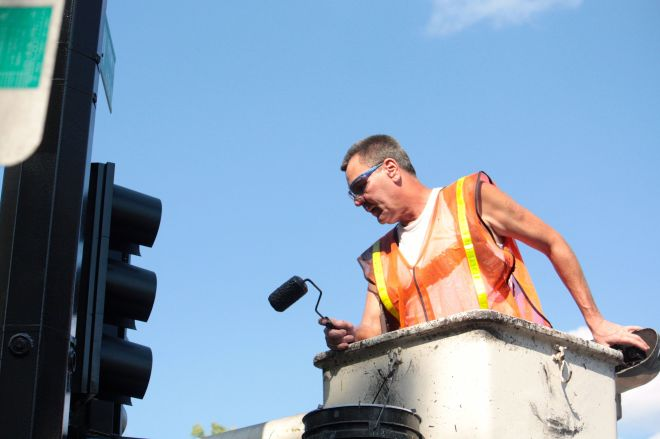 Painter Kerry Koenker checks his work above the intersection of Lexington and Thomas.