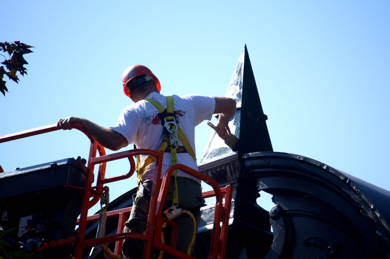More than three stories up, a workman paints one of the finials on the Gardner House condos at 89-97 Leech Street in Uppertown, part of the West End.