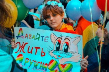 "Young participant at Coming Out's rally for LGBT* rights holds a sign that states ""Let's Live in Peace."" (Photo courtesy of Coming Out)"