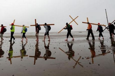 Pilgrims to Lindisfarne walk barefooted across the mudflats