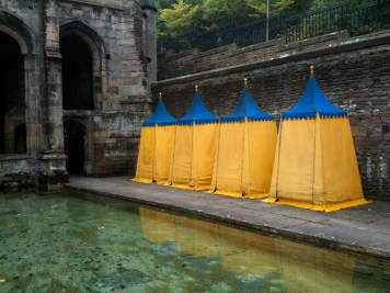 Tents on edge of Holywell for changing into bathing suits to enter the holy waters
