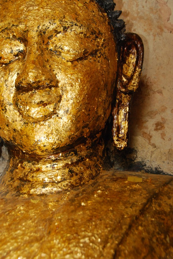 Close-up of a buddha statue with gold leaf applique