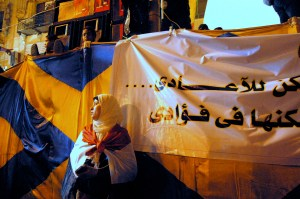 An opposition protester stands near the makeshift stage built in Tahrir Square on the night of July 26, 2013 when President Mohammad Morsi addressed the nation for the last time before the planned June 30th protests. During the demonstrations, women typically gathered near the front of the stage and were separated from men protesters by human chains created by vigilante groups working to protect women against sexual assaults. (SARAH RASHID)