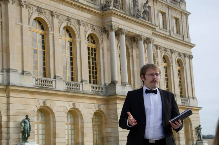 Playing the role of economist John Maynard Keynes, Tom Keating explains his objections to the Treaty of Versailles in front of the palace where it was signed.  (Photo: Benji Preminger)