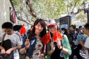 Two Chinese girls show their patriotism with flags and stickers.  This week is a time for Chinese people to join together and be proud of their accomplishments.