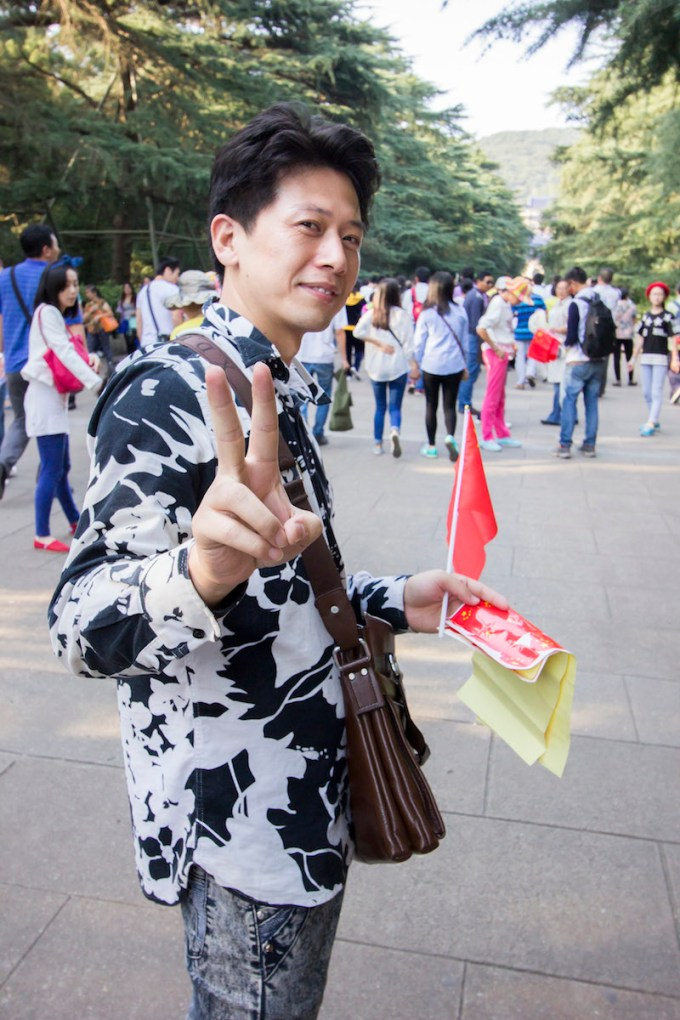 A dealer at Sun Yat-Sen's mausoleum selling flags and stickers for a discount to tourists trying to save a few RMB.