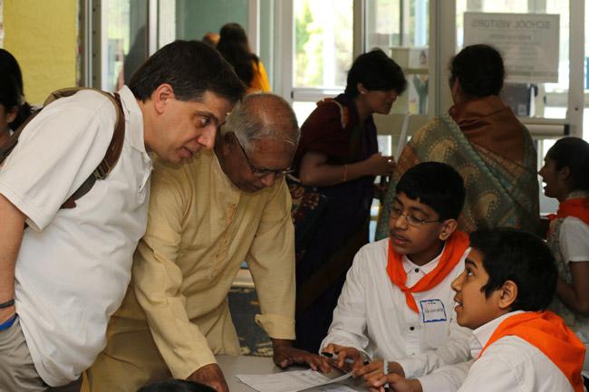 Children welcoming elders to the event