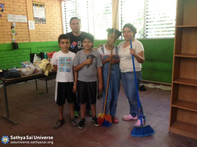 Children and volunteers painting school building
