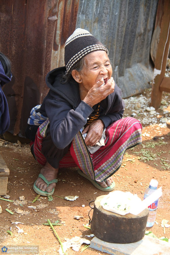 Villager having lunch served by volunteers