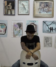 Hasanin surrounded by some of his exhibited works. Image: Hawraa Adnan