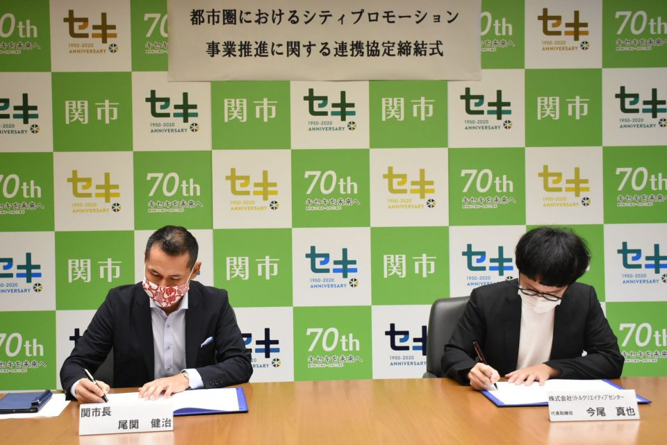 締結式でサインをする尾関関市長と今尾社長。