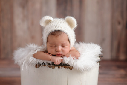 An 11 day old newborn baby girl sleeping in a little, wooden bucket. She is wearing a crocheted, white bear bonnet. Shot in the studio on a wood background.