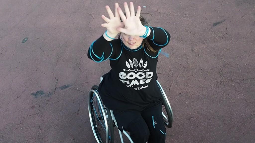 Jacqueline dansend in haar rolstoel van bovenaf gezien, met haar handen voor haar gezicht.
