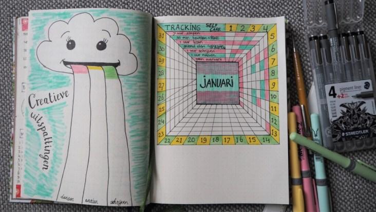 Opengeslagen bullet journal met habit trackers: links een wolkje wat een regenboog uitkotst en rechts een 3D maandtracker van januari