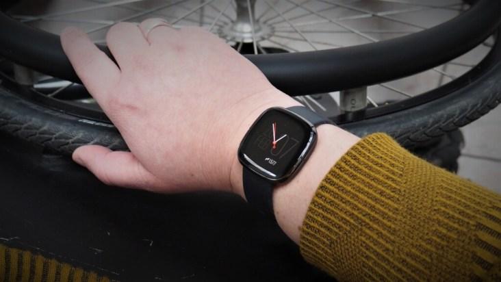 Hand die rolstoelwiel vasthoudt met een Fitbit Sense smartwatch om de pols.