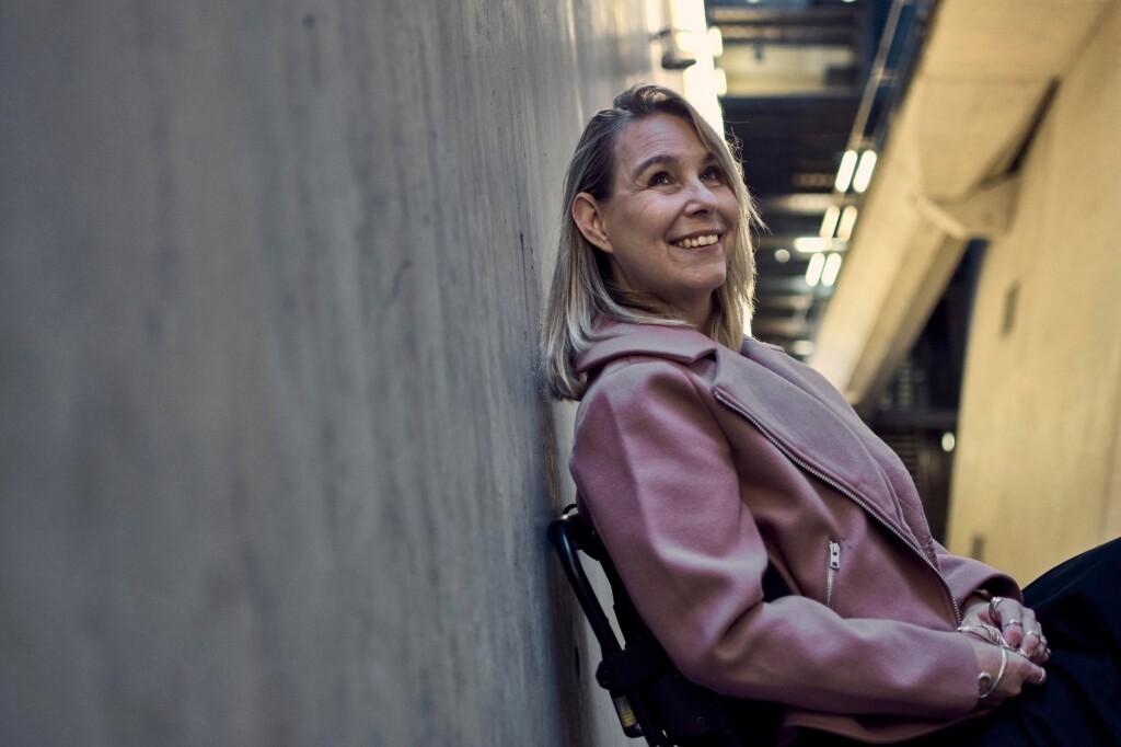 Martine Reesink (auteur Kneus en Co) zittend in een rolstoel en leunend tegen een muur