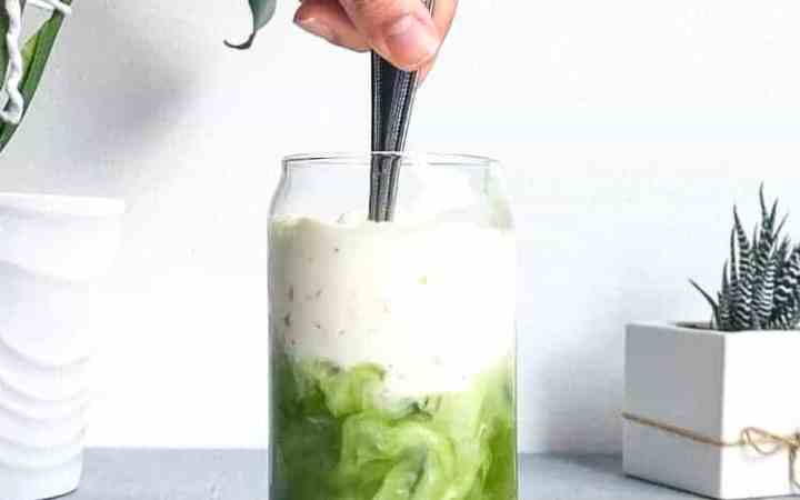 An iced matcha latte being stirred.
