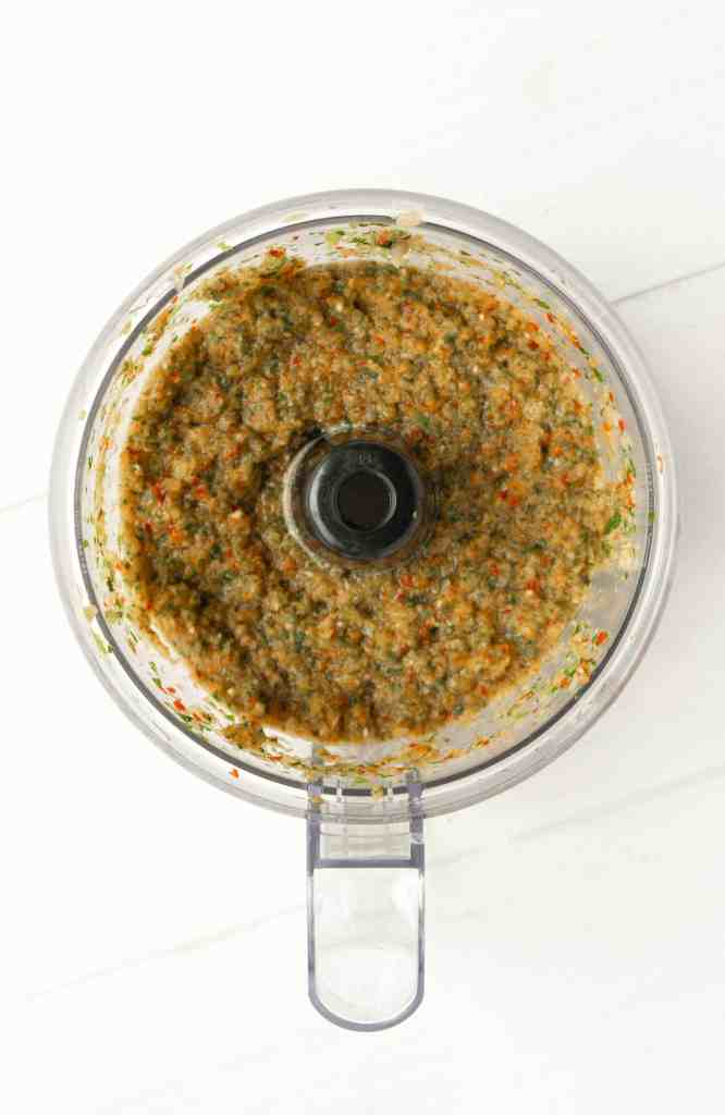 A food processor with ingredients for Puerto Rican Sofrito.