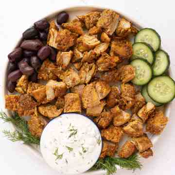 A greek plate of chicken with tzatziki sauce.