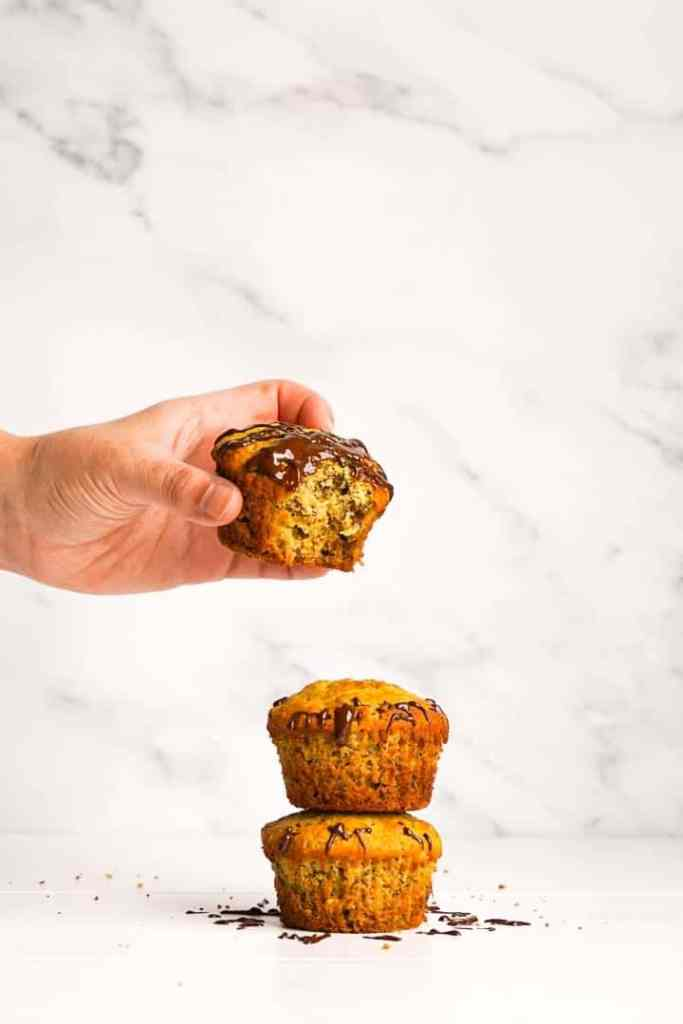 A stack of banana oat muffins with a bite taken.