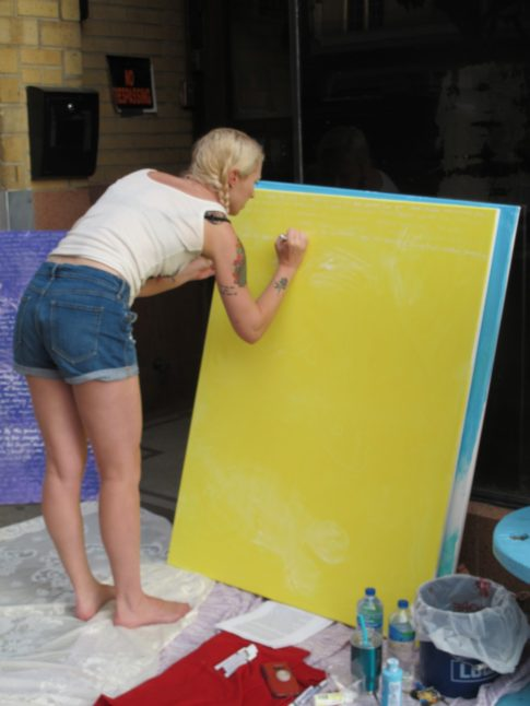 Sally painting on a yellow background