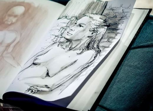 black and white drawing of a woman in a notebook