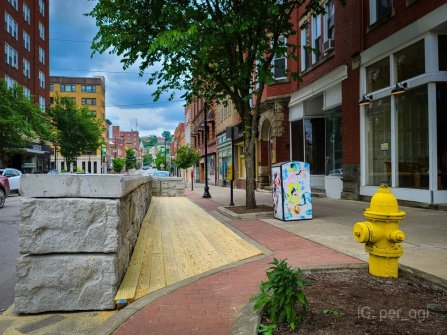 photo of a street with a white trash can covered in multi-colored, abstract paintings of women