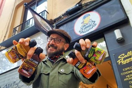 Juan Pariente uno de los propietarios de la tienda Sally Pepper, sujatando con sus manos 4 botellas de las salsas picantes Crazy Lizard