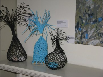 open bias weave in paper string, wire and can with pebbles