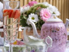 champagne in glass with strawberries vintage tea set and flowers in background